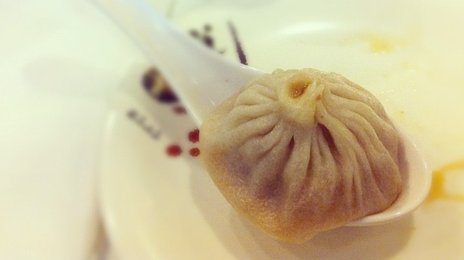 A <em>xiao long bao</em>, or soup dumpling, in a large spoon.