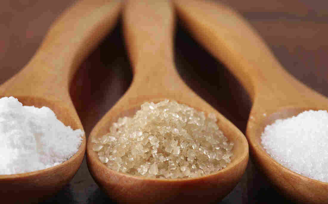 Three wooden spoons with different kinds of sugar in each.