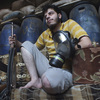 Gas mask in one hand and rifle in the other, a Free Syrian Army fighter sits inside a house in the city of Homs early Thursday.