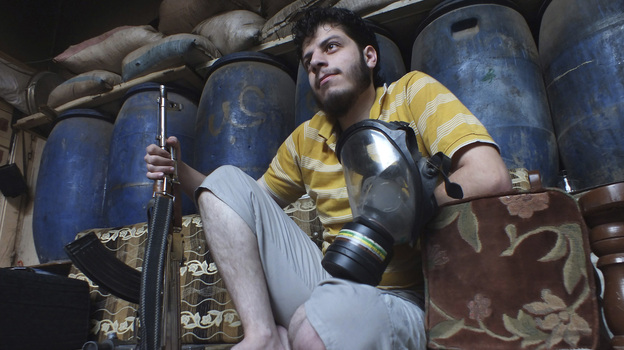 Gas mask in one hand and rifle in the other, a Free Syrian Army fighter sits inside a house in the city of Homs early Thursday. (Reuters /Landov)