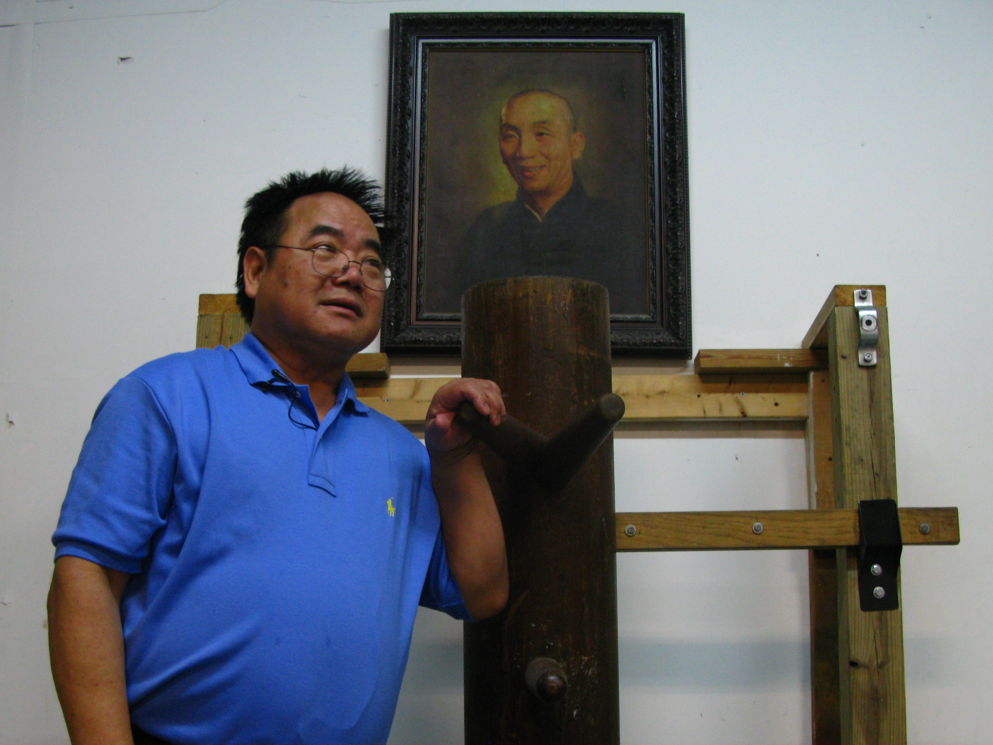 Allan Lee, 64, at his kung fu studio in Queens, N.Y. Lee began studying Wing Chun-style kung fu under Ip Man (seen in portrait) and his disciples almost 50 years ago.