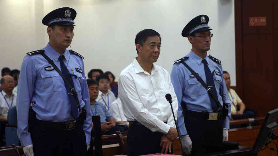 In this photo released by the Jinan Intermediate People's Court, Bo Xilai appears Thursday on the first day of his trial in eastern China's Shandong province. Interestingly, he was photographed flanked by two very tall policemen.