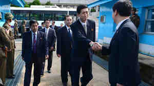North Korean delegate Pak Yong-Il crosses the military demarcation line with South Korea for a meeting on family reunions as North Korean soldiers stand guard at the border village of Panmunjom on Friday.