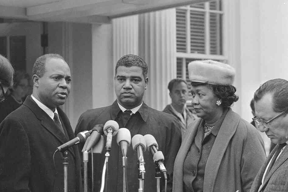 Three of the six leaders of African-American organizations who met with President Lyndon B. Johnson Nov. 19, 1964, talk with reporters at the White House after the meeting. They are, left to right: James Farmer, national dire