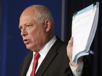 Illinois Gov. Pat Quinn holds a bill that he said would suspend Illinois lawmakers' pay during a news conference in Chicago on July 10.