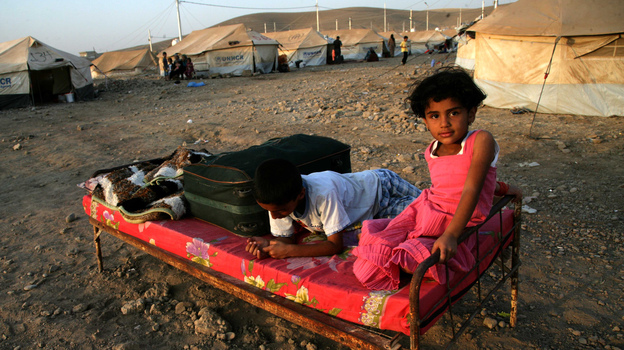 Syrian-Kurdish children sit on a bed at the Quru Gusik refugee camp in the Kurdish region of northern Iraq, on Aug. 22. Faced with brutal violence and soaring prices, thousands of Syrian Kurds have poured into Iraq's autonomous Kurdish region. UNICEF has reported that over one million Syrian children live as refugees in other countries. (AFP/Getty Images)