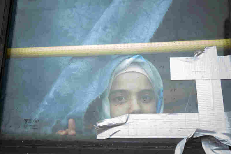 A Syrian girl looks through the window of a bus where she has lived with her family for the past eight months at a refugee camp in Bab al-Salam, Syria near the Turkish border, on Feb. 28.