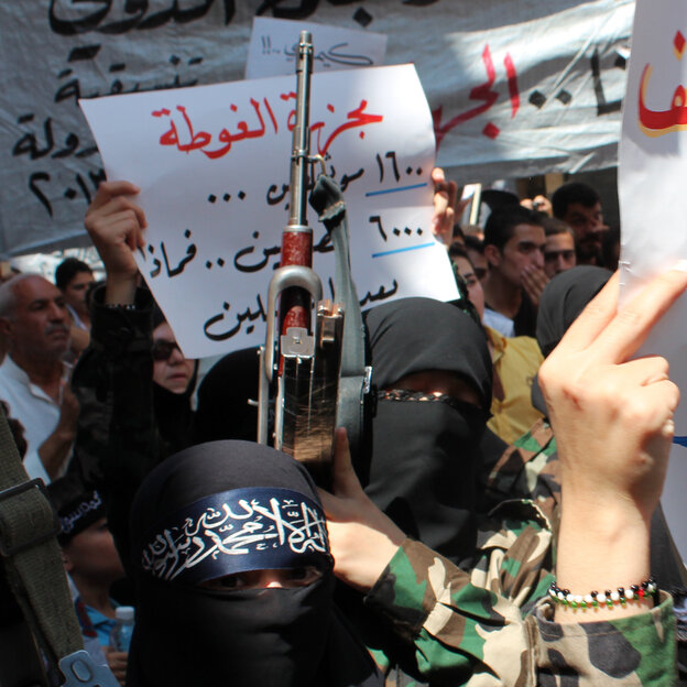 Female rebel fighters gather in Syria's northern city of Aleppo on Saturday to protest what they claim was a chemical attack by pro-government forces in a suburb of Damascus.