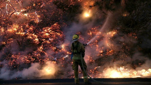 A firefighter uses a hose to douse the flames of the Rim Fire on Saturday near Groveland, California. (Getty Images)