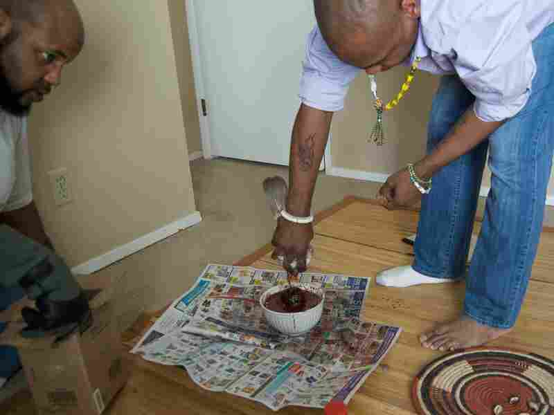 Wesley Hunt, left, and Ifagbemi perform a ritual in his suburban apartment for the gods of Yoruba.
