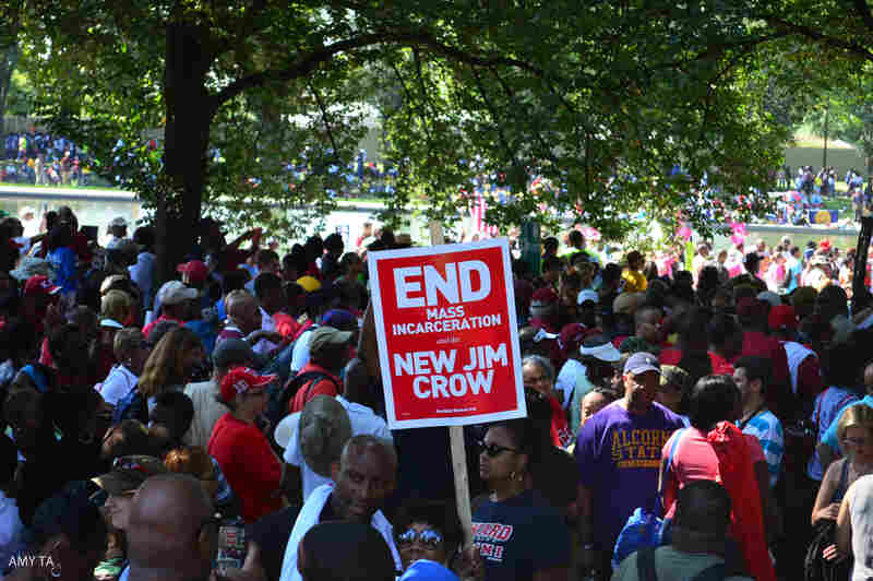 """A marcher holds the sign: """"End Mass Incarceration and the New Jim Crow."""""""