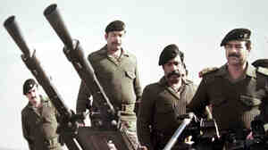 Then-Iraqi dictator Saddam Hussein (at right) behind an artillery piece during the Iraq-Iran war. (An undated photo from the 1980s.)