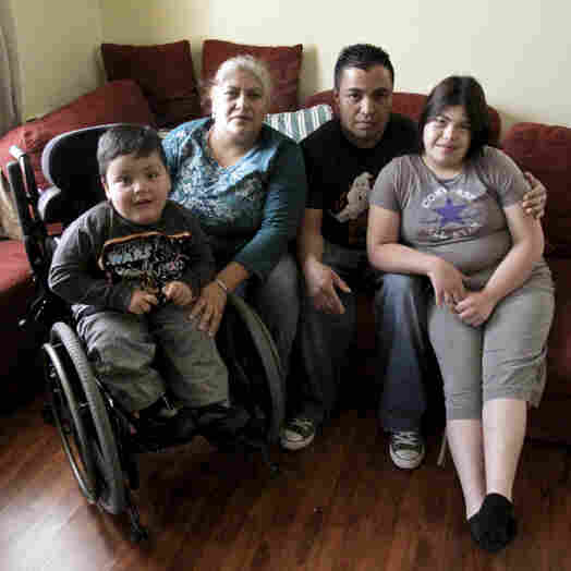 The local playground's design doesn't work for Emmanuel, shown here with his family. The loose surface hampers his wheelchair, and there are no ramps to help him get onto the play structures.