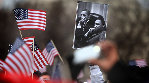 A spectator on the National Mall holds an image of President Obama and Martin Luther King during the 2013 presidential inauguration in January. (MCT/Landov)