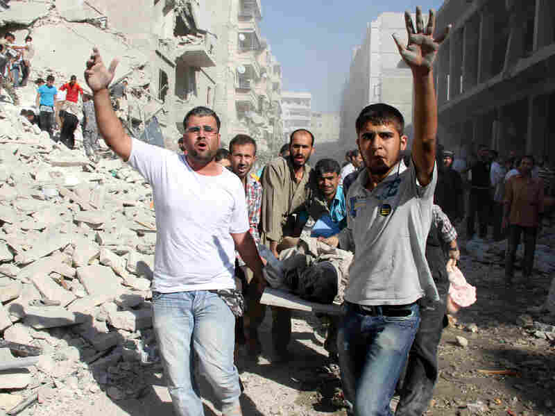 Syrian men evacuate a victim following an airstrike by government forces in the northern city of Aleppo on Monday. World attention has been focused on a possible chemical weapons attack last week in Damascus, but the war rages on in other parts of the country as well.