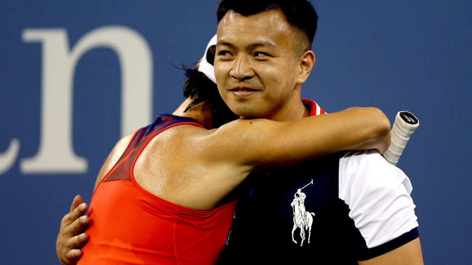 Francesca Schiavone of Italy hugs a ball boy during her first-round women's singles loss to Serena Williams at the 2013 U.S. Open Monday night. (Getty Images)