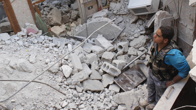 In Aleppo, Syria, on Monday, this Free Syrian Army fighter stood in the rubble of a building that has collapsed during fighting there. (Reuters/Landov)
