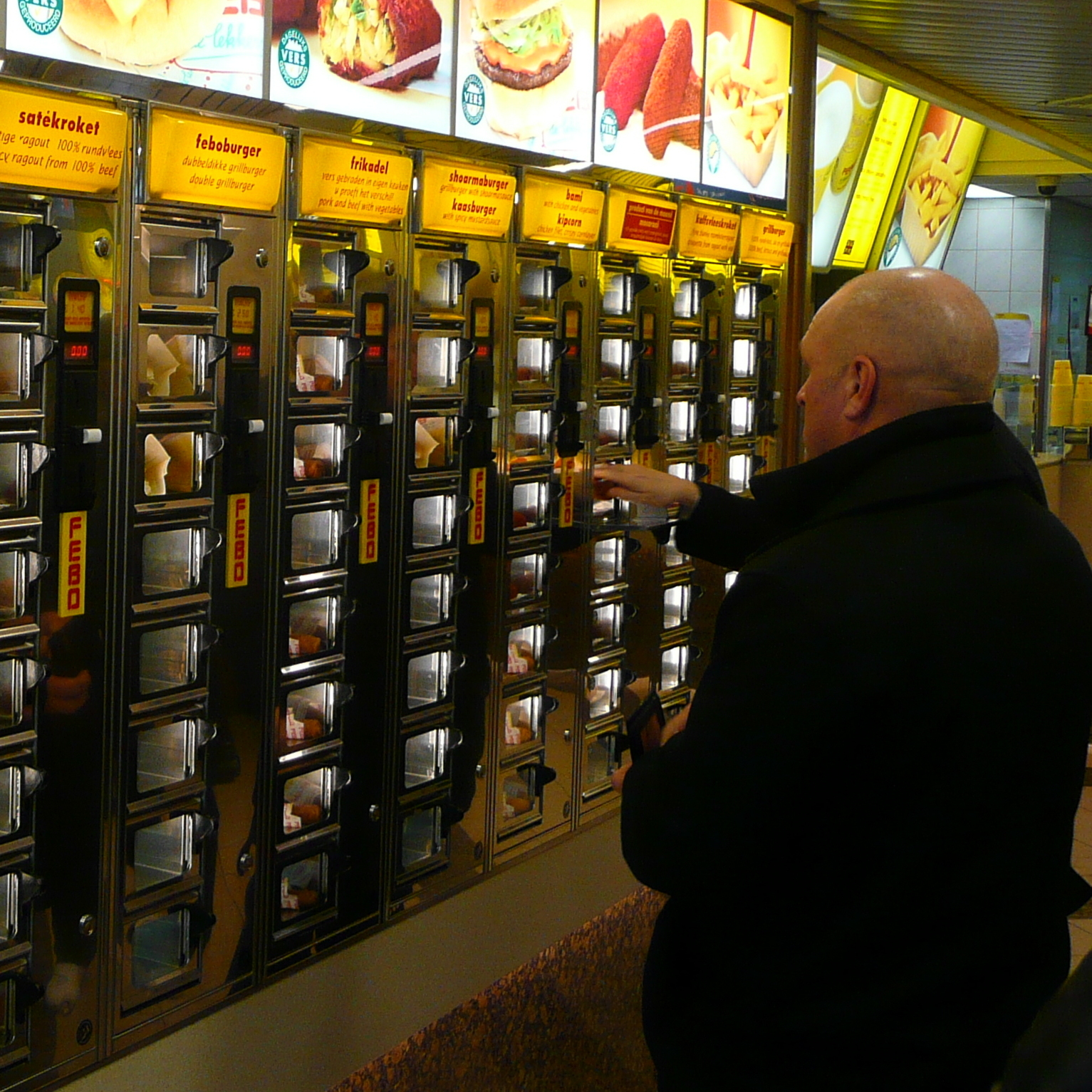 Customers choose from various hot foods available at one of Amsterdam's Febo vending machines.