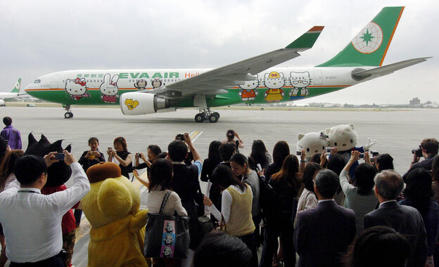 """Local journalists take photos of EVA airplane decorated with """"Hello Kitty"""" during a press preview in Taoyuan in 2005."""