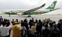 Local journalists take photos of EVA airplane decorated with