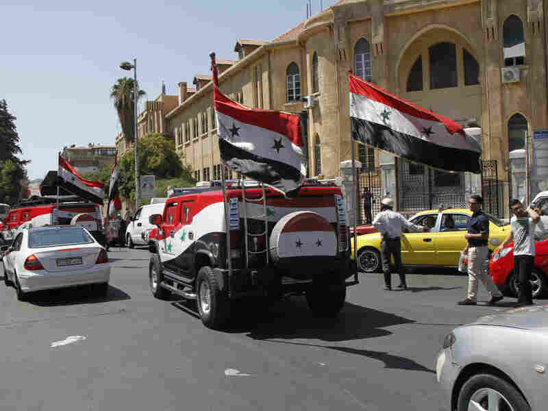 Vehicles carrying Syria's national flag and playing songs in support of President Bashar Assad drive through the streets of Damascus on Wednesday.