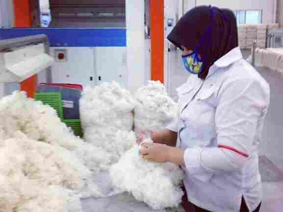 Other than this woman spot-checking some of the cotton, no human hands touch the yarn. It's all machines, shooting strings of cotton, twisting and twirling and winding.