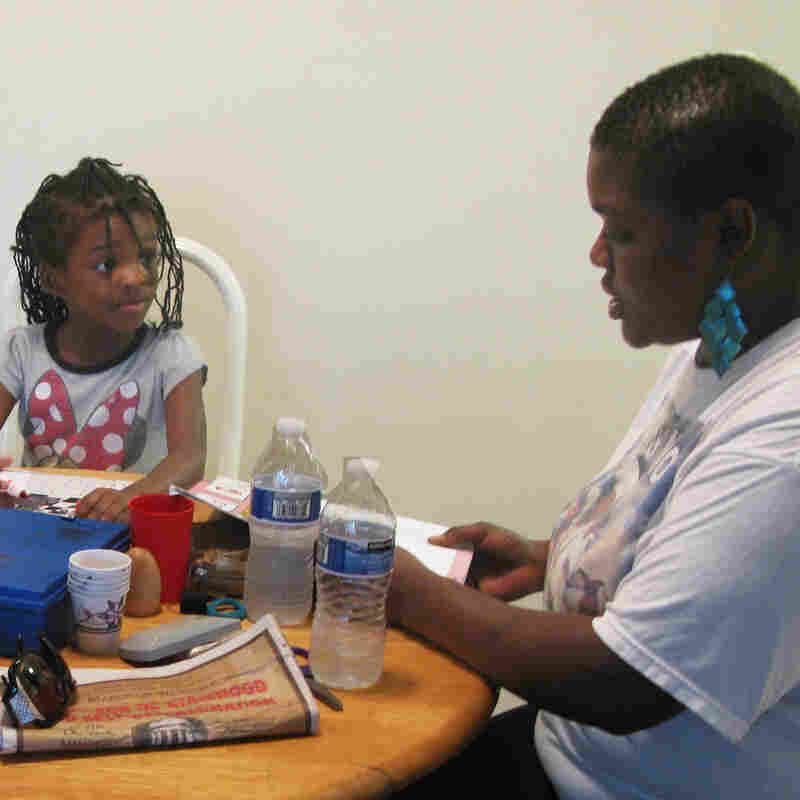Losia Nyankale helps daughter Jonessa and son Juliean learn the alphabet. Nyankale, who works in a restaurant in Washington, D.C., says she needs food stamps and child-care subsidies to make ends meet.