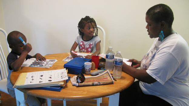 Losia Nyankale helps daughter Jonessa and son Juliean learn the alphabet. Nyankale, who works in a restaurant in Washington, D.C., says she needs food stamps and child-care subsidies to make ends meet. (NPR)