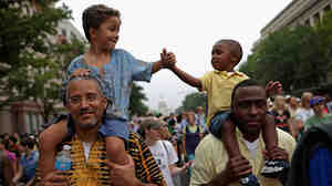 John Mbugua and his son Giovanni Mbugua, 6, of San Jose, Calif., and Lavon Johnson and his son Mason Johnson, 2, of Fort Meade, Md., greet one another while marching with thousands of other people from Capitol Hill to the Lincoln Memorial on Wednesday.