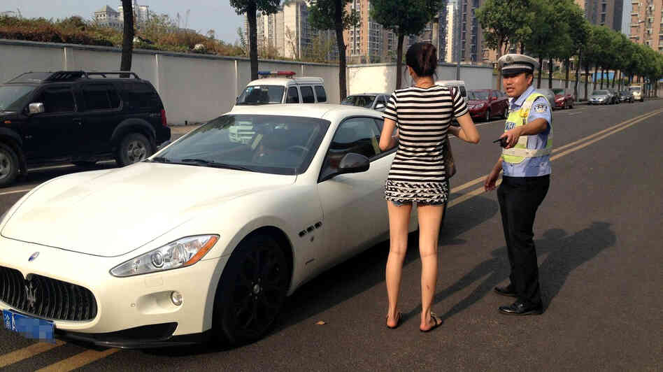 A police officer tickets a young woman for parking a Maserati (estimated to be worth more than $300,000) on the double yellow lines in the middle of the street in Chongqing, China. Stories like this one that go viral in China are increasingly available to English audiences, thanks for a new breed of websites such as ChinaSMACK.