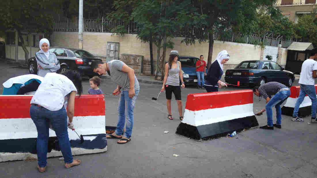 Young people in the Syrian capital, Damascus, paint concrete roadblocks with the colors of the Syrian flag. With the threat of a U.S. strike growing, there are public displays of support for the Syrian state.
