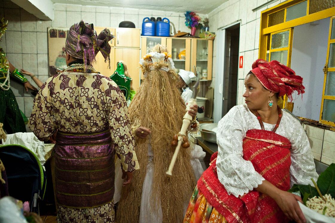 Femme préparer la nourriture pour Orixas dans la cuisine du Candomblé?  temple.  Le prêtre et les gens habillés comme les esprits traversent pour entrer dans la pièce principale pour la cérémonie.
