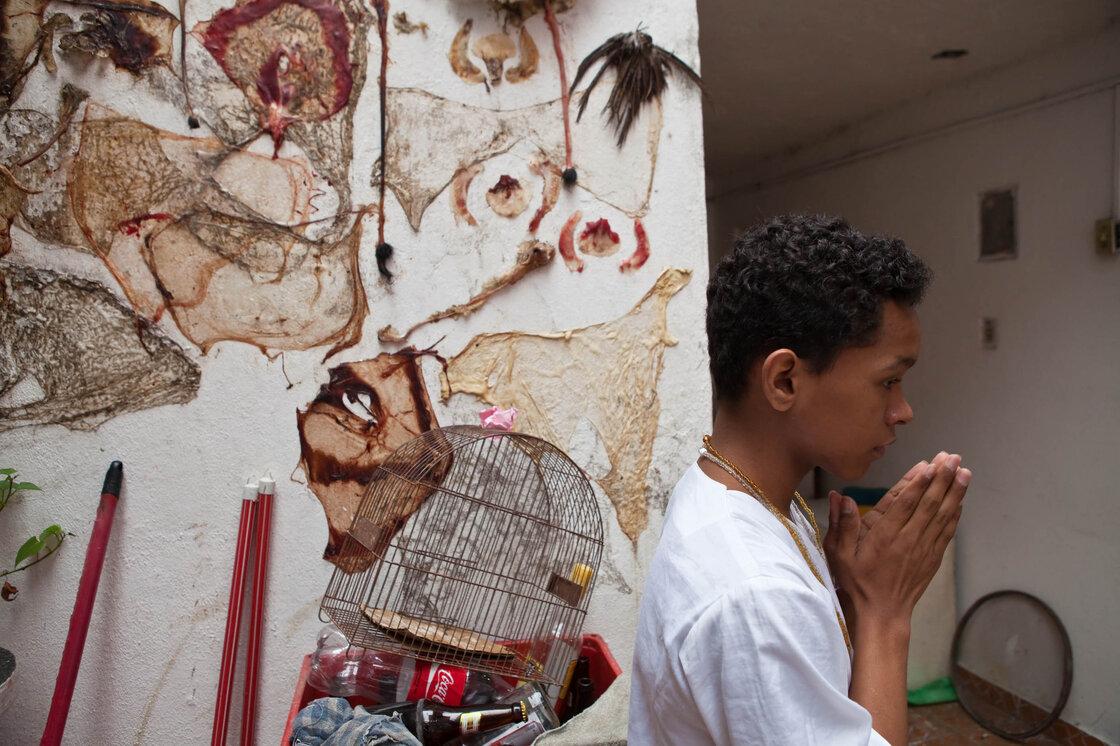 Un jeune médecin se prépare pour la fête près d'un mur décoré de peaux d'animaux sacrifiés et les entrailles.  Les animaux ont été sacrifiés rituellement la veille et seront servis à la fête.