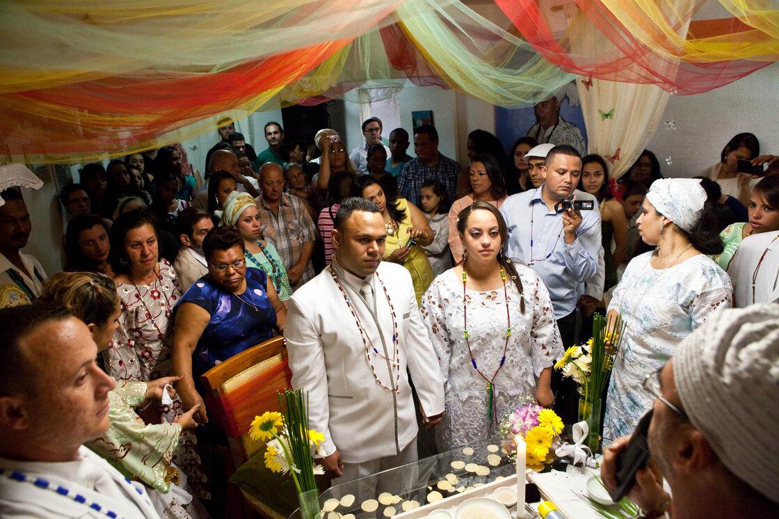 Après être entré dans la salle au son des tambours et le Candomblé?  chansons, le couple écoute de prêtre Leonardo Tadeu Alves.