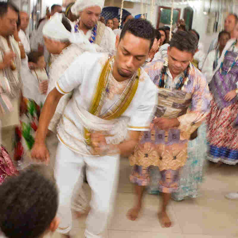 Men possessed by orixas dance before getting dressed in orixa costumes. They are participating in an Olubaje party, a Candomblé ritual for cleansing life of bad things and healing. The main god at the party is Omulu (the one with straws), known for healing diseases.
