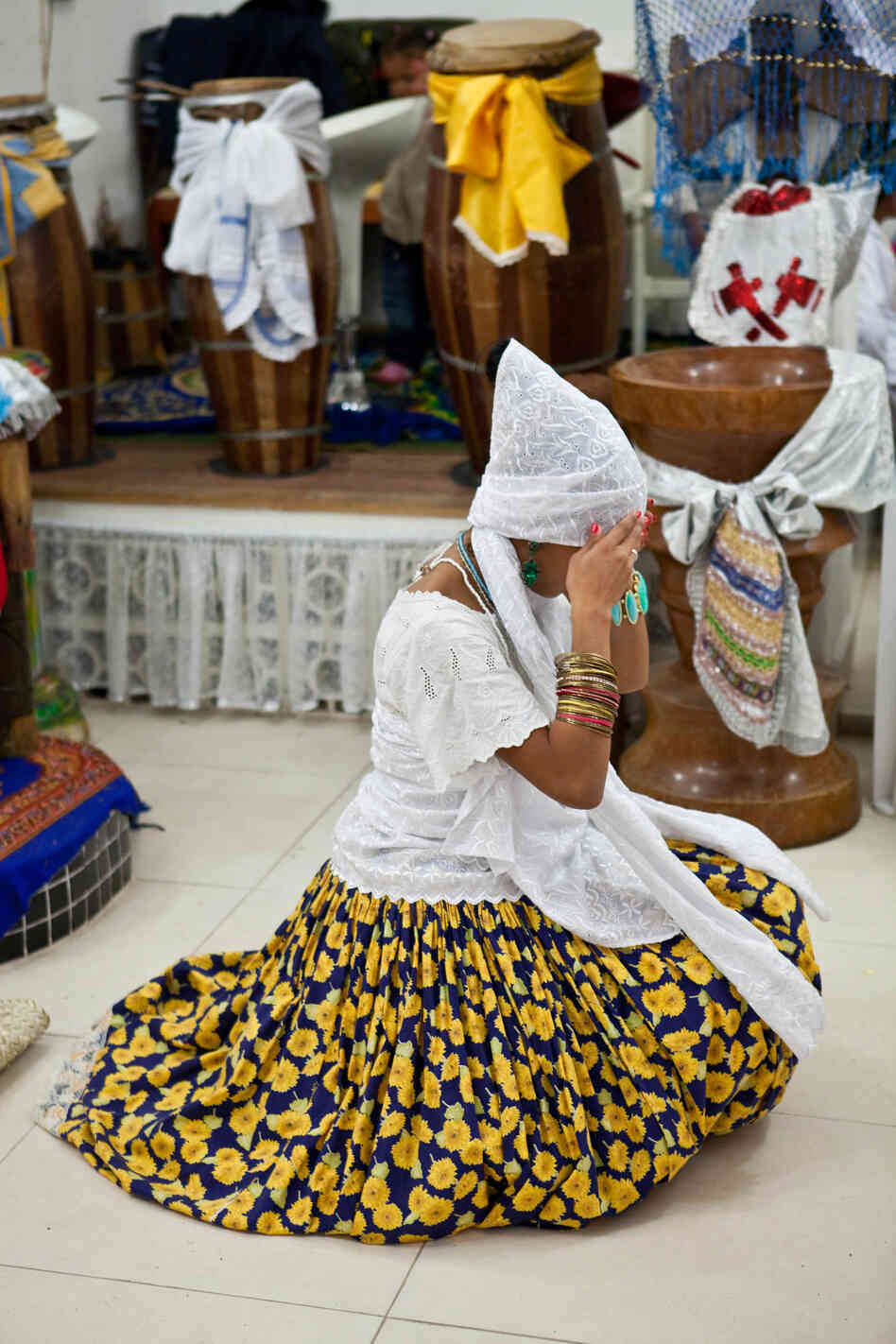 """Une femme fixe son turban tandis que les praticiens effectuent """"danse nettoyage"""" avant la manifestation des Orixas."""