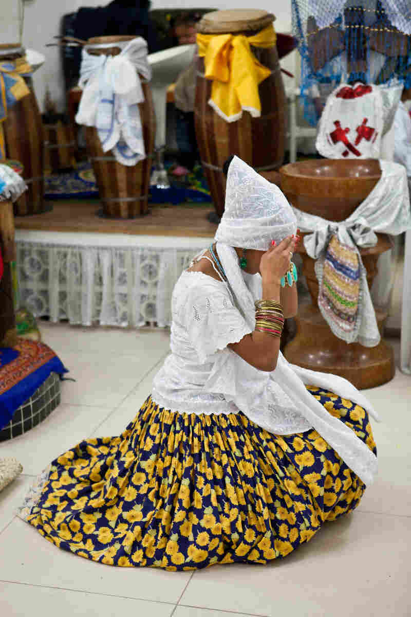 "A woman fixes her turban while practitioners perform ""cleaning dancing"" before the manifestation of the orixas."