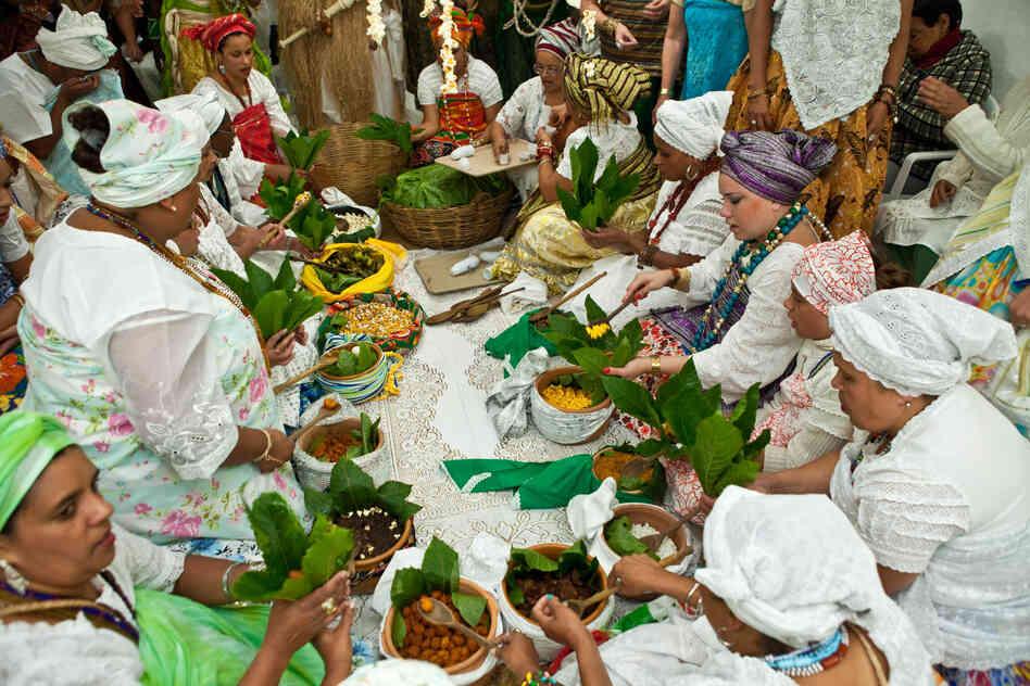 Les gens servent de la nourriture sacrée à la fête Olubaje.  L'aliment est emballé dans des feuilles de la plante de l'huile de ricin.