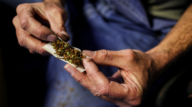 A customer rolls a joint made of half marijuana and half tobacco to smoke inside of Frankie Sports Bar and Grill in Olympia, Wash., in December 2012. (Reuters/Landov)