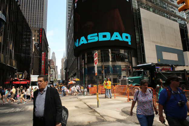 People in New York City walk by the Nasdaq stock market one day after the the electronic exchange experienced a a three-hour trading delay due to a technical problem.