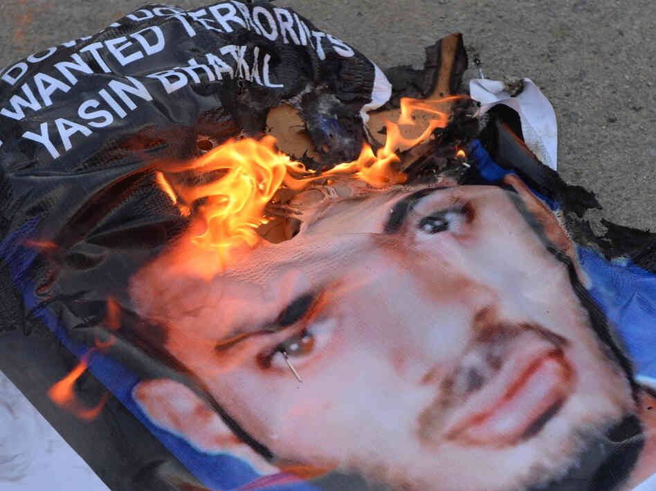 A poster of Yasin Bhatkal, an alleged founder of the Indian Mujahideen, burns after being set on fire by demonstrators