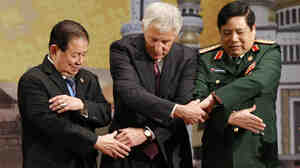 """U.S. Defense Secretary Chuck Hagel, center, chains his hands with his counterparts from Vietnam, right, and Thailand before the ASEAN meeting in Bandar Seri Begawan, Brunei, on Thursday. The trip's message: The U.S. is committed to its """"rebalance"""" toward the Asia-Pacific region."""