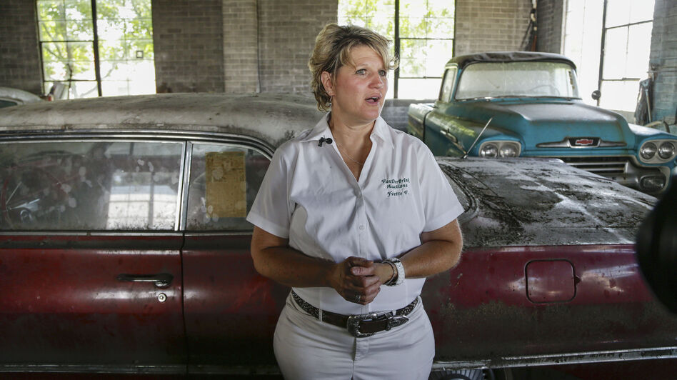 Auctioneer Yvette VanDerBrink in front of a 1963 Chevrolet Impala and a 1958 Cameo pickup truck at the Lambrecht Chevrolet car dealership. (AP)