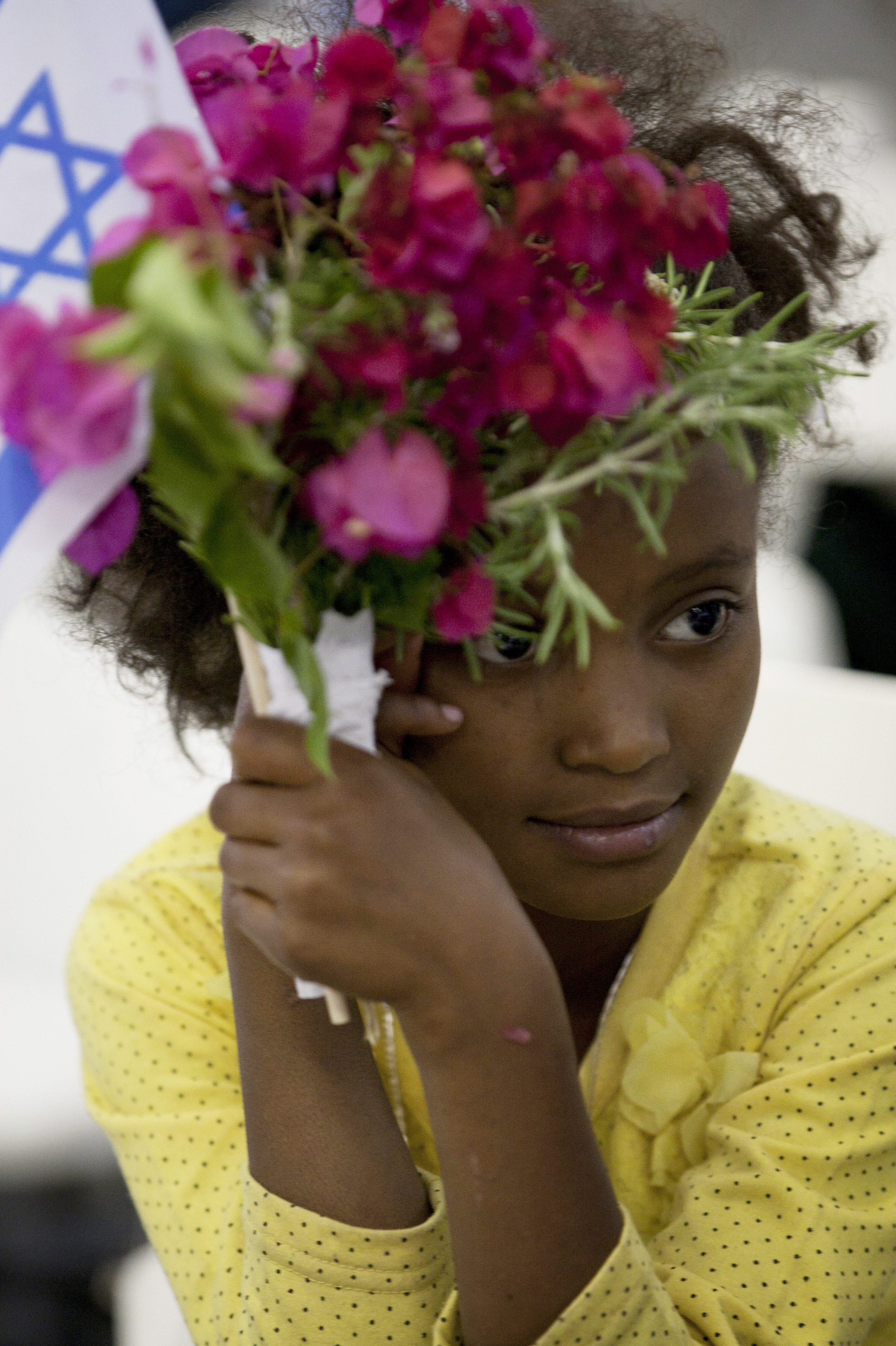 A newly immigrated Ethiopian Jewish girl holds flowers and a flag as she attends a welcoming ceremony at Ben Gurion airport near Tel Aviv, Israel, on Oct. 29, 2012. The Israeli government's program to bring Jews from Ethiopia officially ended this week.