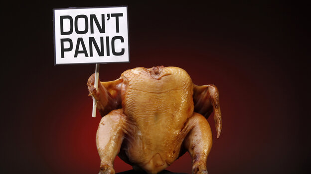 "A prepared turkey holding a sign that reads ""Don't Panic""."