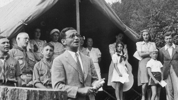"""American composer Irving Berlin sings his song """"God Bless America"""" in front of Boy Scouts troop members and spectators gathered at a tent in Monticello, New York in 1940. Instead of collecting royalties from """"God Bless America,"""" Berlin created a fund that collected and distributed them to the Boy and Girl Scouts."""
