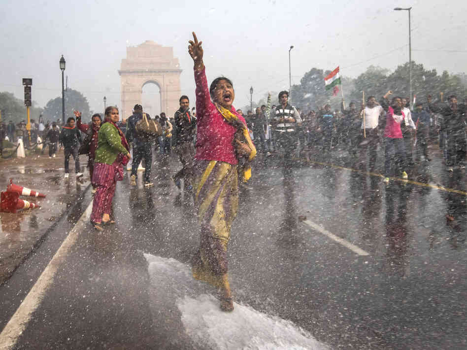 A protester in India chants slogans as she braces herself against the spray fired from police water canons during a protest in December sparked by the gang rape of a 23-ye