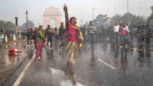 A protester in India chants slogans as she braces herself against the spray fired from police water canons during a protest in December sparked by the gang rape of a 23-year-old paramedical student.