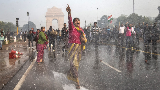 A protester in India chants slogans as she braces herself against the spray fired from police water canons during a protest in December sparked by the gang rape of a 23-year-old paramedical student. (Getty Images)