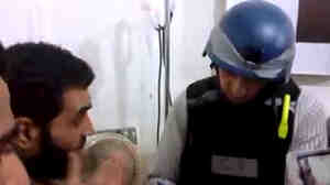An image grab taken from a video posted by Syrian activists earlier this week allegedly showing a U.N. inspector listening to the testimony of a man in the Damascus suburb of Moadamiyet al-Sham.
